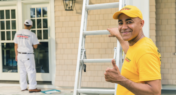 Painter in yellow shirt smiling and giving thumbs up outside of house