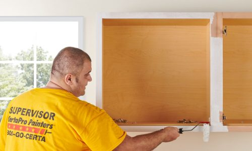 man painting edge of cabinet on wall