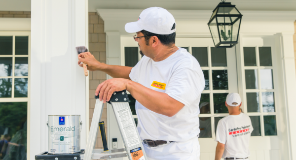 Painting the exterior house trim and siding.