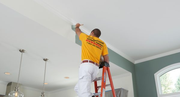interior house painter finishing painting a wall