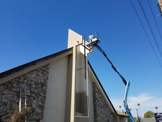 painter on boom lift working on church
